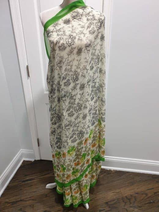 black and white sari with green border and pink, green, and yellow flowers